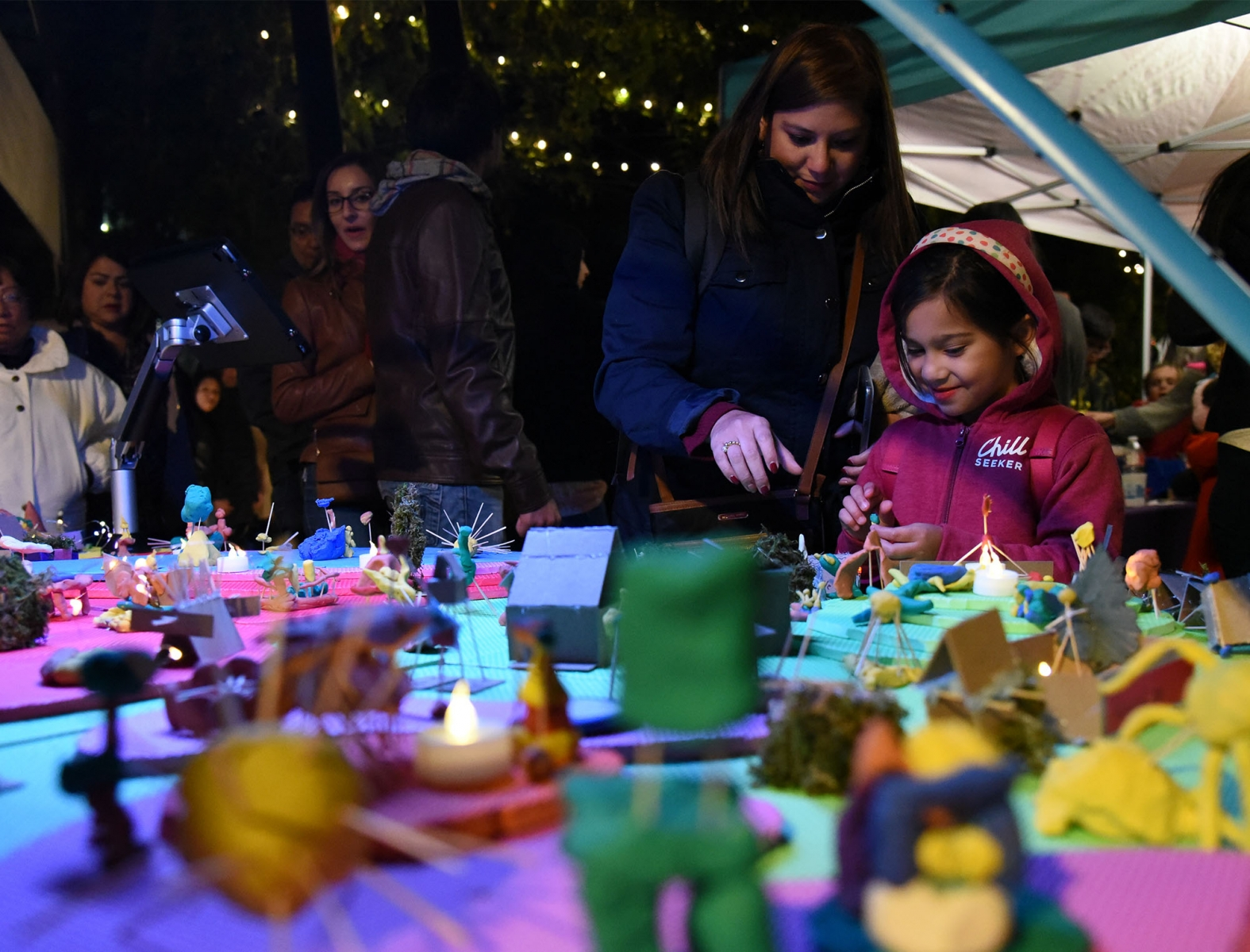 Cynthia Martinez helps daughter Sierra Borrego place her creation in a mock town created Nov. 11 during Luminaria. <em><b>Photo by V. Finster | Heron</b></em>