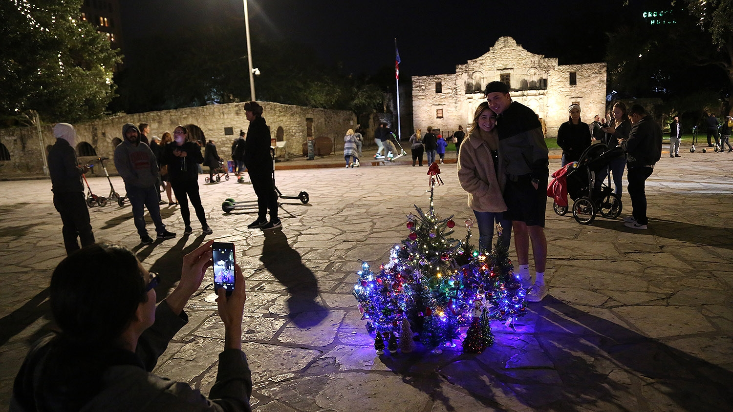 Steven Monreal takes a photo of a young couple with roughly 40 mini Christmas trees Sunday night at Alamo Plaza. <em><b>Photo by Ben Olivo | Heron</b></em>