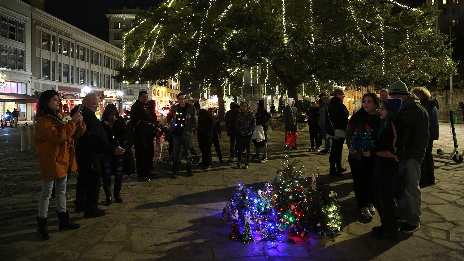People get their picture taken with mini Christmas trees that were placed in front of the Alamo Sunday night. The gathering was a protest of the 50-foot tree's relocation to Travis Park last year. <em><b>Photo by Ben Olivo | Heron</b></em>