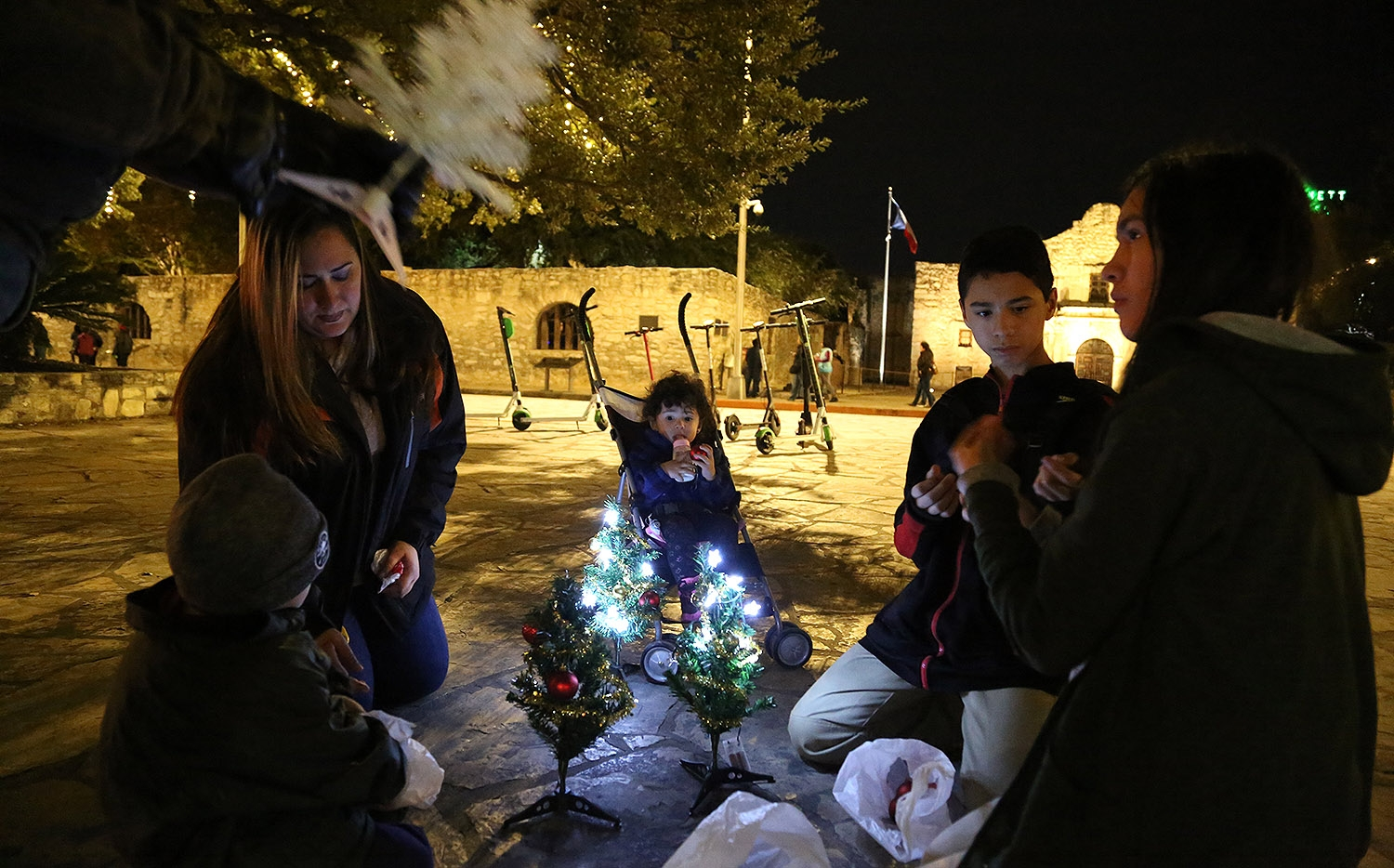 Members of the Gomez / Cuellar family prepare mini Christmas trees to join others in front of the Alamo Sunday night. <em><b>Photo by Ben Olivo | Heron</b></em>
