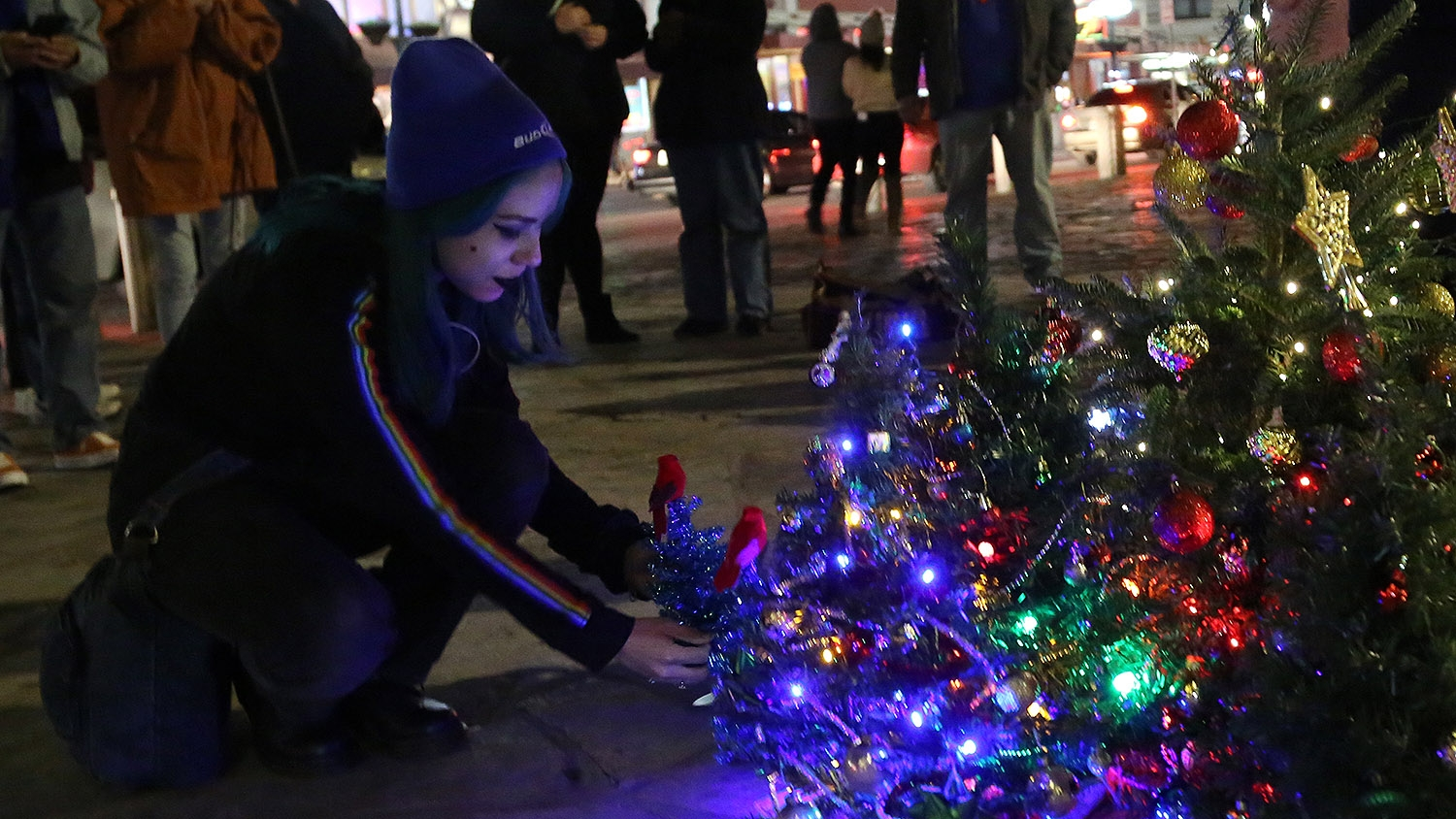 Maria V.G. Perez, 17, places a small Christmas tree topped with a cardinal with a few dozen other little trees at Alamo Plaza Sunday night. <em><b>Photo by Ben Olivo | Heron</b></em>