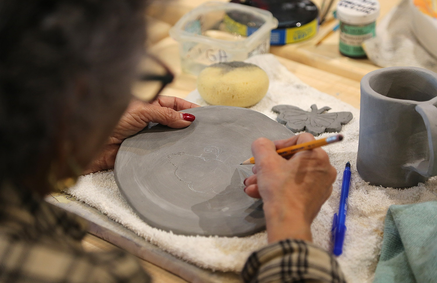 Olga Martinez, 75, works on a clay plate Feb. 2 at MujerArtes on the near West Side.