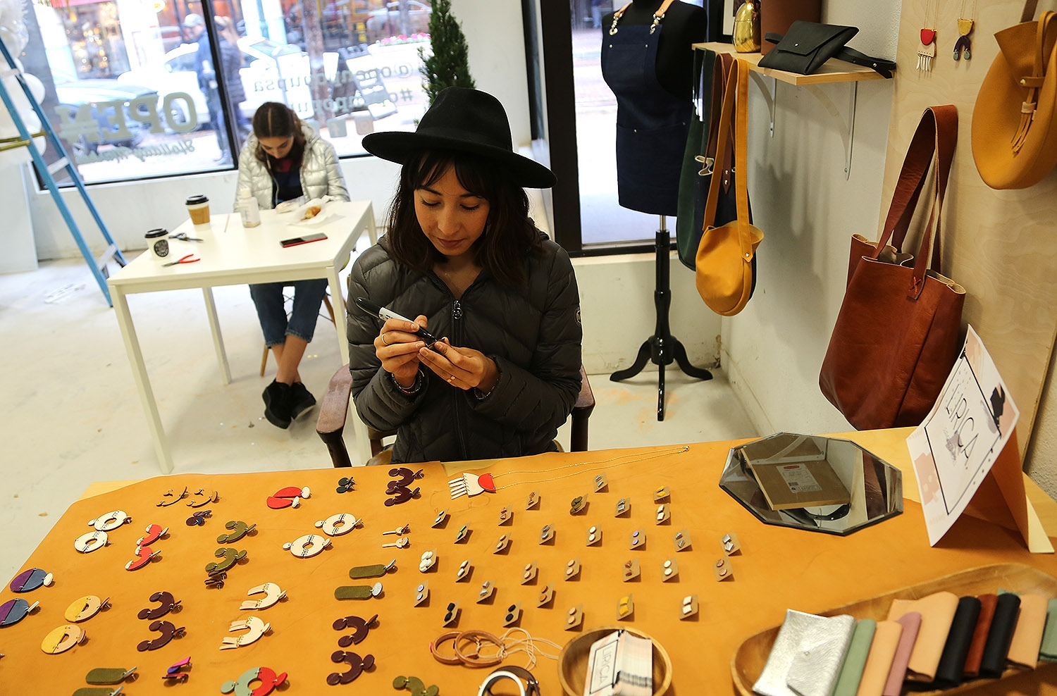 Maria Galvan with Lirica, leather accessories, sets up for the  OPEN Holiday Market. <em><b>Photo by Ben Olivo | Heron</b></em>