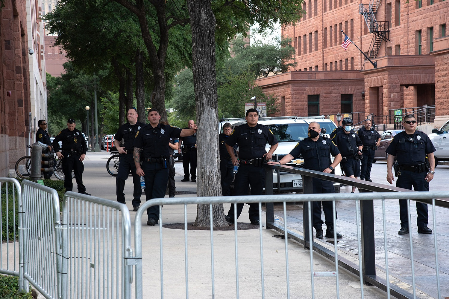 San Antonio police officers stand behind a fence while watching protestors Thursday, June 4 on W Nueva St. Photo by V. Finster | Heron Contributor