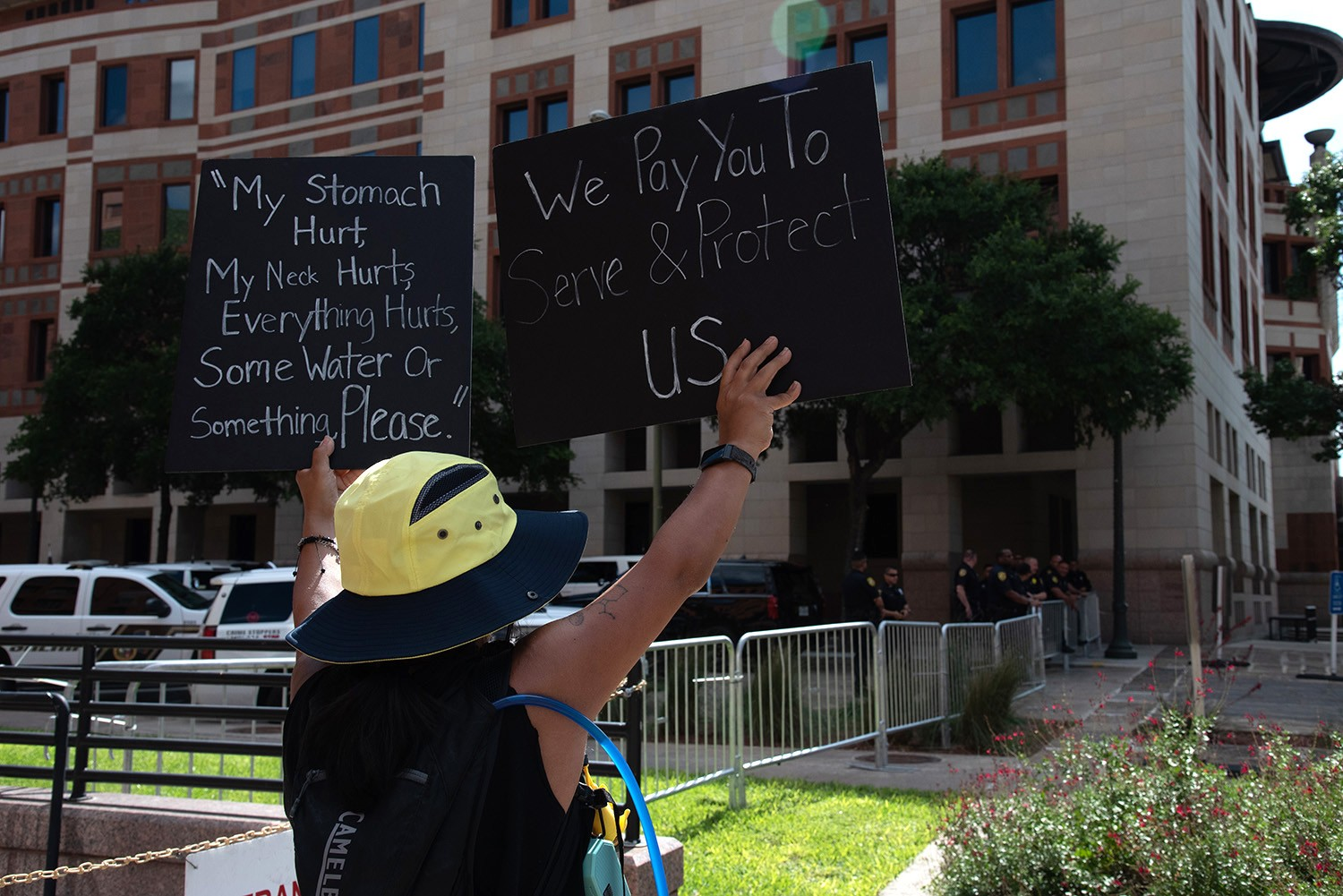 Protestors Katherine Torres, 31, holds signs up towards San Antonio police officers in front of the Bexar County Courthouse, Thursday, June 4.Photo by V. Finster | Heron Contributor