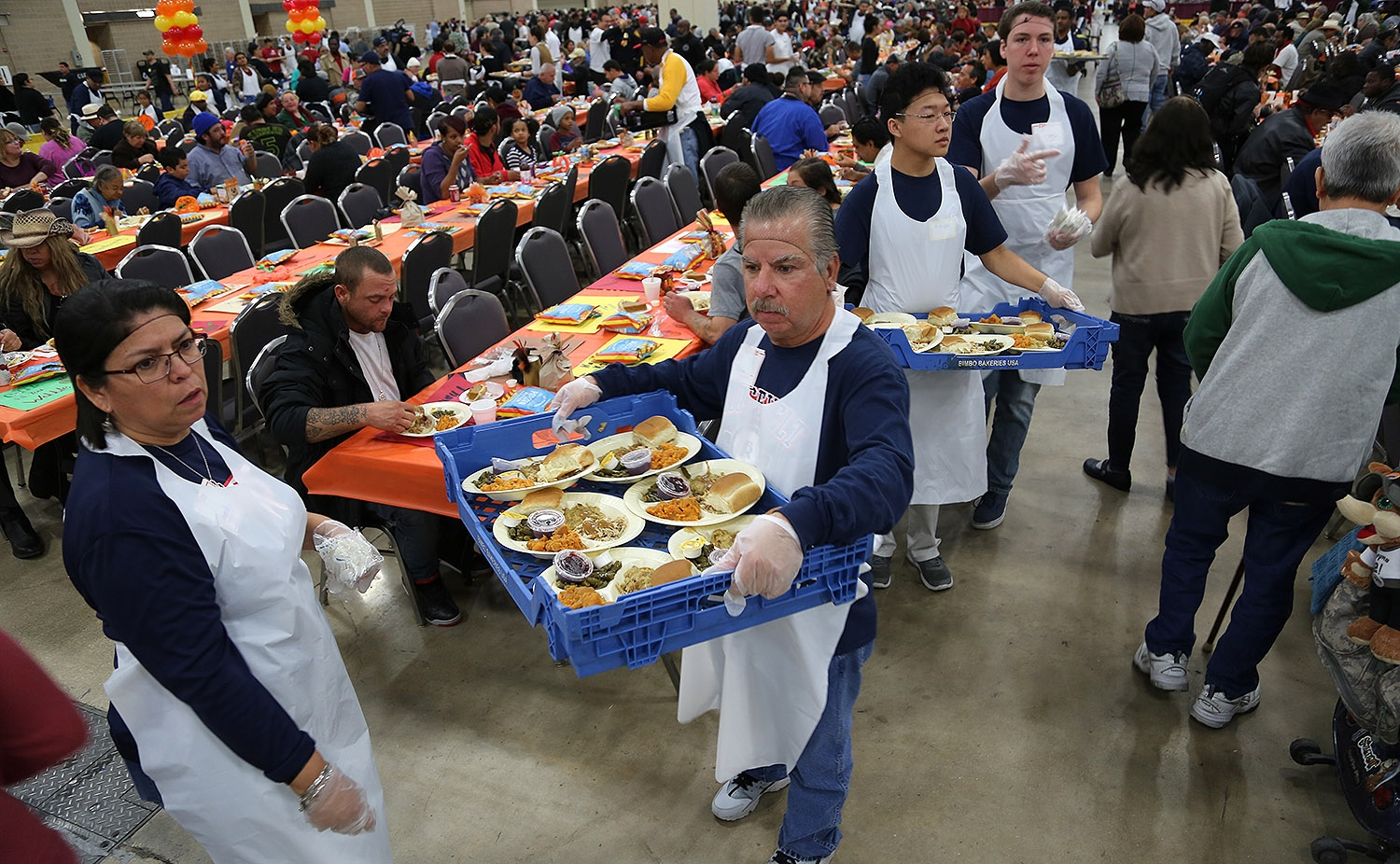 Julian Errisuriz, 57, a volunteer, searches for people in need of their first plate at the Raul Jimenez Thanksgiving Dinner Thursday. <em><b>Photo by Ben Olivo | Heron</b></em>
