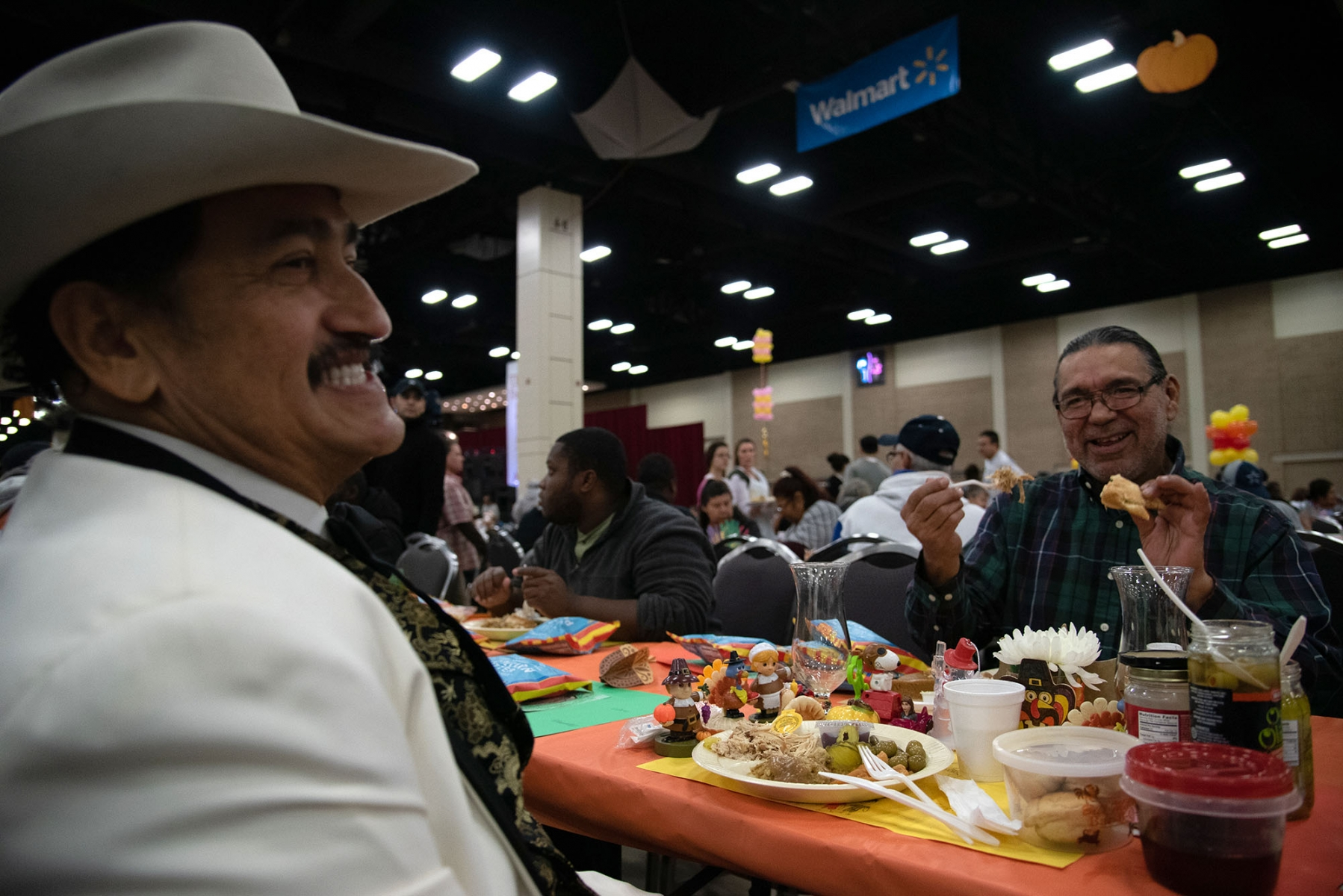 "Robert Torres (left), 59, and Cesar Laijas, 56, share a laugh at the Raul Jimenez Thanksgiving Dinner Thursday at the Henry B. Gonzalez Convention Center. The two single men have become friends the past four Jimenez dinners. ""We're just single men who have been by ourselves,"" said Torres, who brought additional condiments and several turkey tchotchkes as decorations. <em><b>Photo by V.Finster 