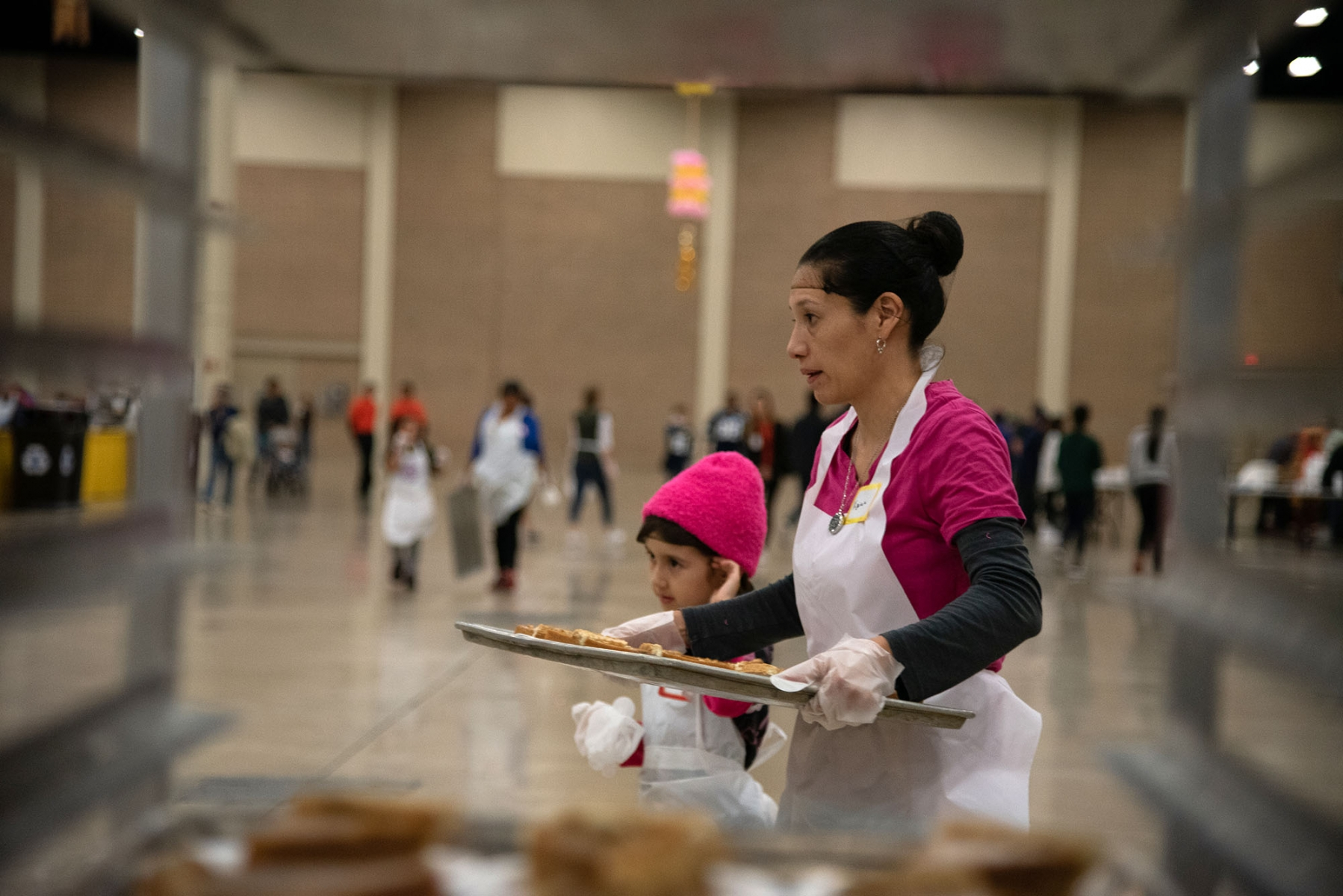 Volunteers Virginia and Amelia Plessinger walk to deliver pumpkin pie during the Raul Jimenez Thanksgiving Dinner Thursday at the Henry B. Gonzalez Convention Center. <em><b>Photo by V.Finster | Heron</b></em>