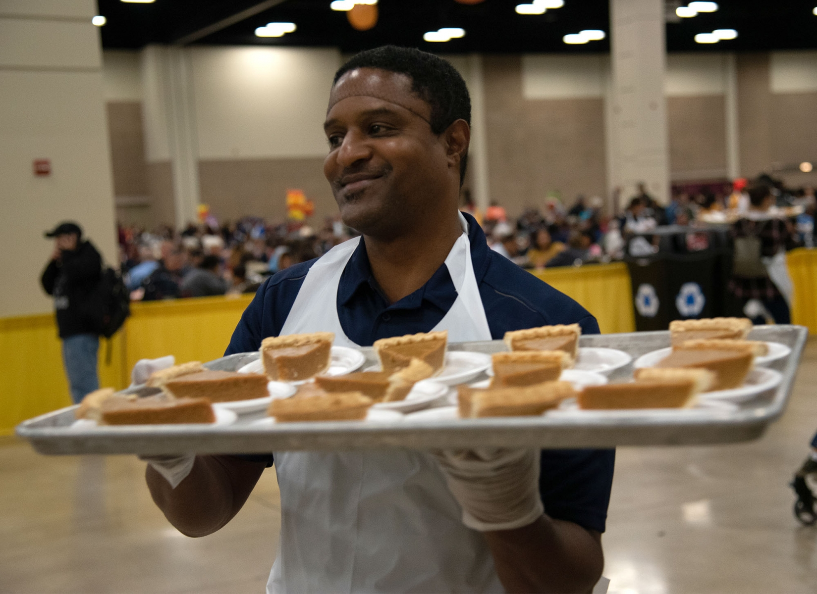 Volunteer Darius Dunn carries a tray of pumpkin pie during the Raul Jimenez Thanksgiving Dinner Thursday at the Henry B. Gonzalez Convention Center. <em><b>Photo by V.Finster | Heron</b></em>