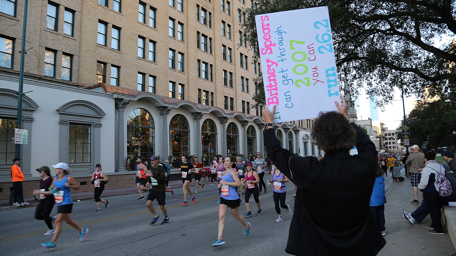 Denise Gatian, 56, cheers on runners in the Rock 'N' Marathon Sunday. <em><b>Photo by Ben Olivo | Heron</b></em>