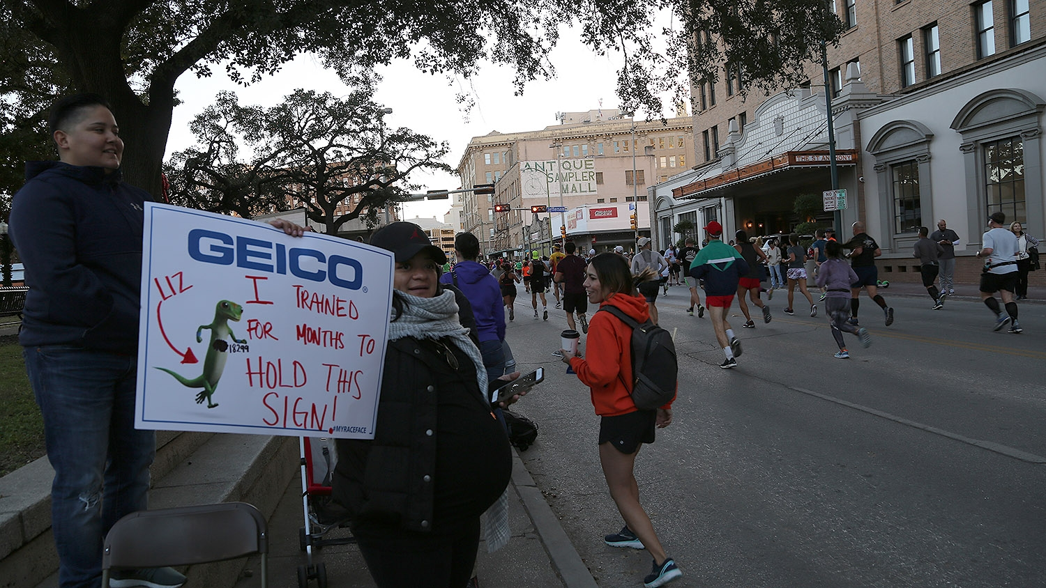 Adrianna Zamudio, 36, holds a sign in support of the runners in the Rock 'N' Roll Marathon on Sunday. <em><b>Photo by Ben Olivo | Heron</b></em>