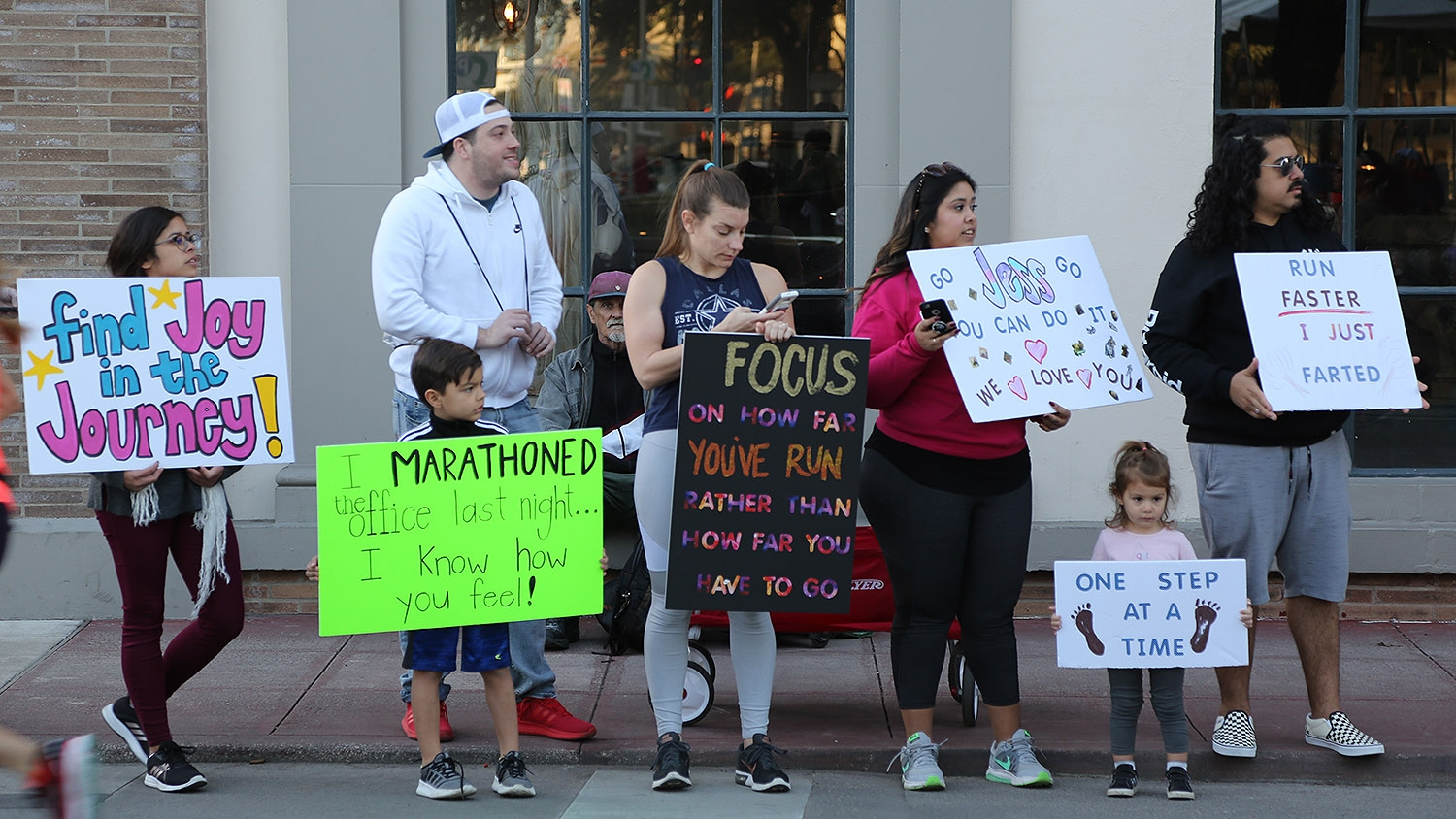 Members of the Segura family—Becca (from left) Lyric, Angelica, Sage and Gilbert—cheer on runners during the Rock 'N' Roll Marathon Sunday morning. <em><b>Photo by Ben Olivo | Heron</b></em>