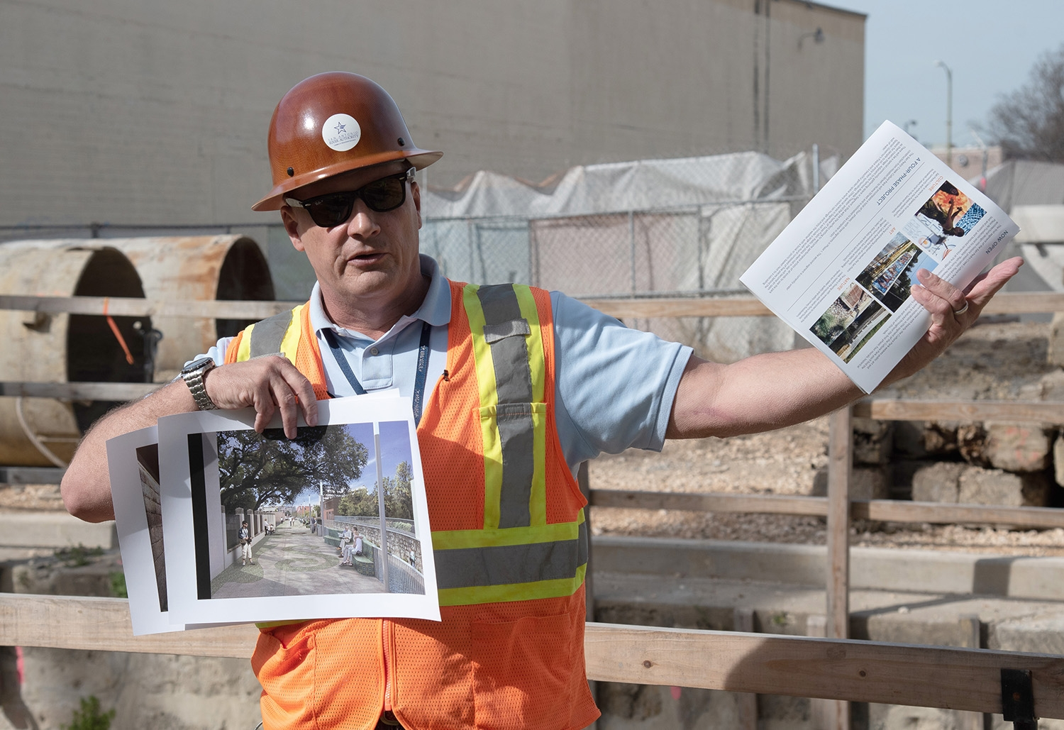 Kerry Averyt, senior engineer and project manager for the San Antonio River Authority, holds renderings while speaking during a tour over the second segment of the San Pedro Creek Culture Park Feb. 15.