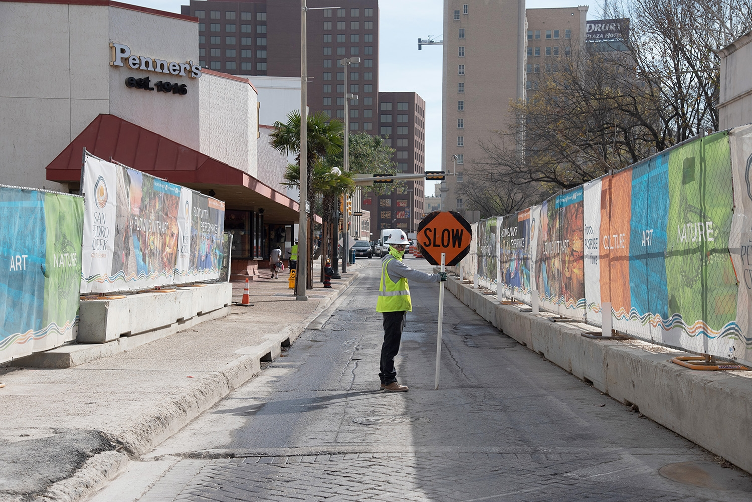 A construction worker holds a signs to slow traffic during a tour over the second segment of the San Pedro Creek Culture Park Feb. 15.