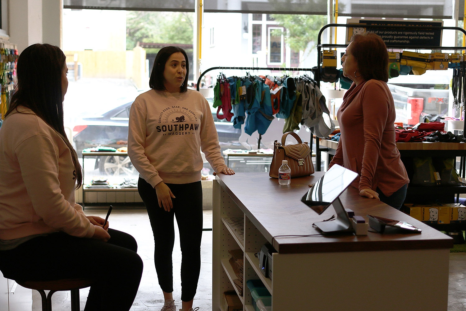 Maricela Guerra (center) speaks with Jacklyn Giddens (left) and her mother Laticia Castro at SouthPaw Waggery, 317 Lexington Ave., Suite 4. <b><em>Photo by Noah Alcala Bach | Heron contributor</em></b>