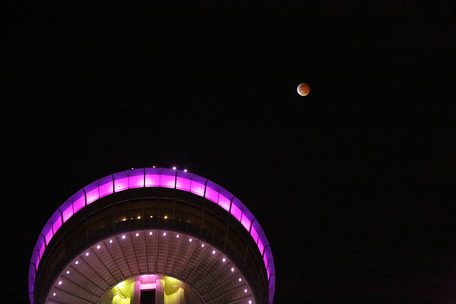 The super blood wolf moon hovers above the Tower of the Americas late Sunday night. Photo by Ben Olivo | Heron