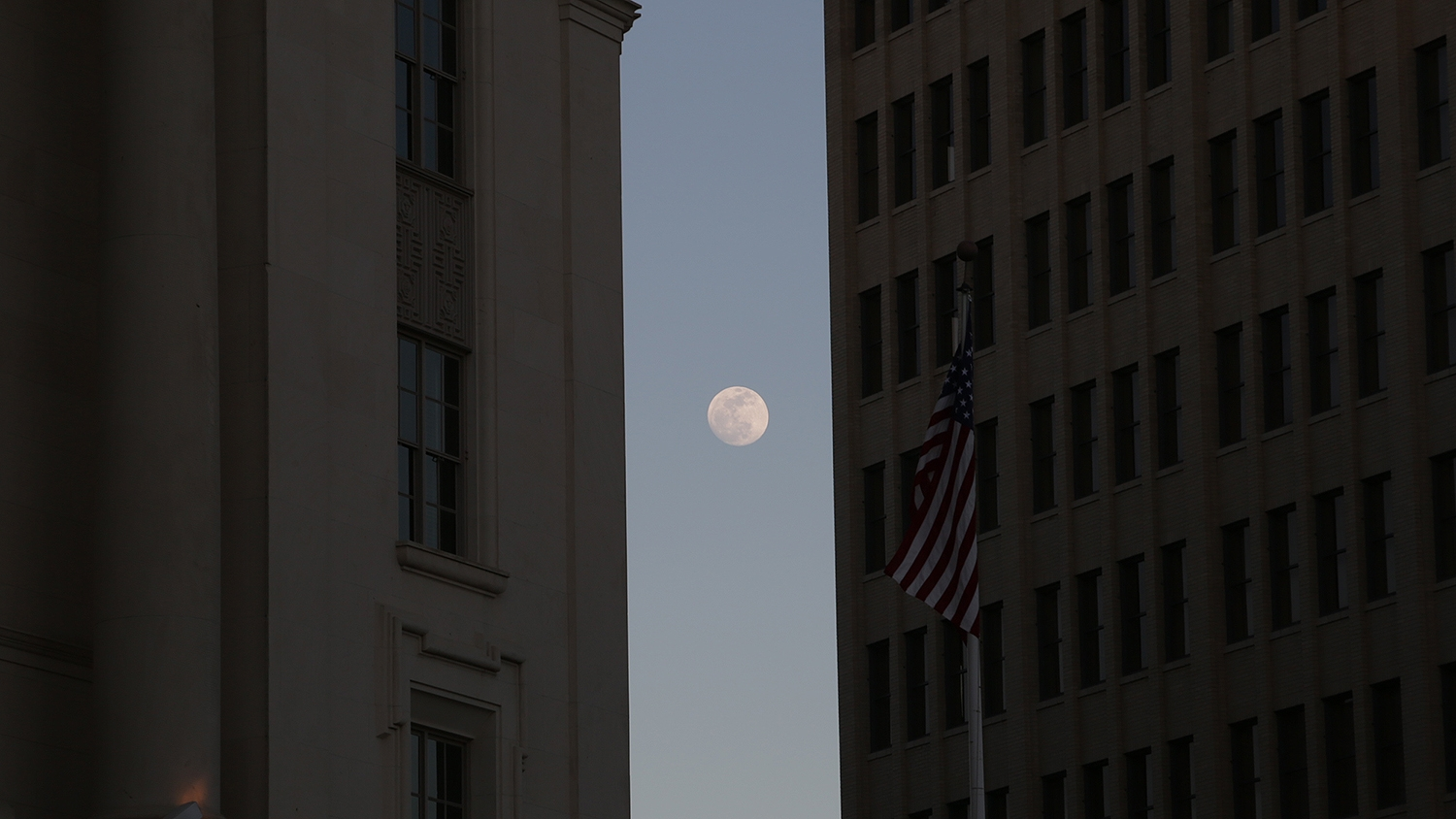 The moon rests between the Hipolito F. Garcia Federal Building and U.S. Courthouse and the Emily Morgan hotel early evening Saturday. Photo by Ben Olivo | Heron