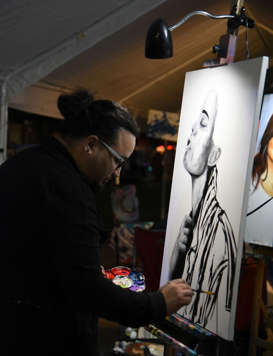 Artist Adrian De La Cruz paints during the 10th annual Una Noche en La Gloria Oct. 20 on Guadalupe St. <em><b>Photo by V. Finster | Heron</b></em>