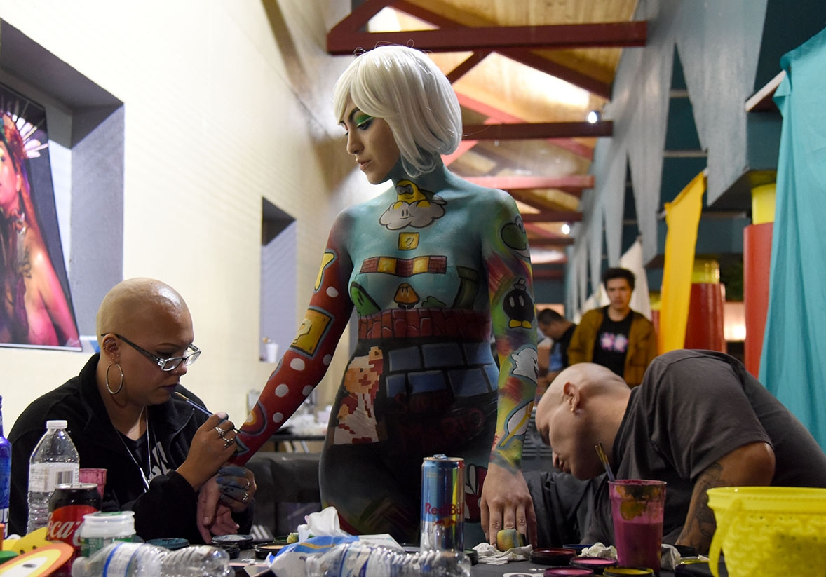 Amber Gonzales and Sohlo, artists with Beyond The Canvas, paint a Mario themed design on model Eileen Rodrigues during the 10th annual Una Noche en La Gloria Oct. 20 on Guadalupe St. <em><b>Photo by V. Finster | Heron</b></em>