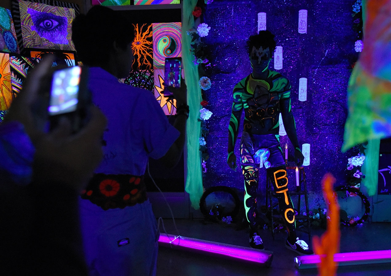 Rebecca Rojas, artist with Beyond The Canvas, takes a photo of her artwork and model Brandon Afa during the 10th annual Una Noche en La Gloria Oct. 20 on Guadalupe St. <em><b>Photo by V. Finster | Heron</b></em>