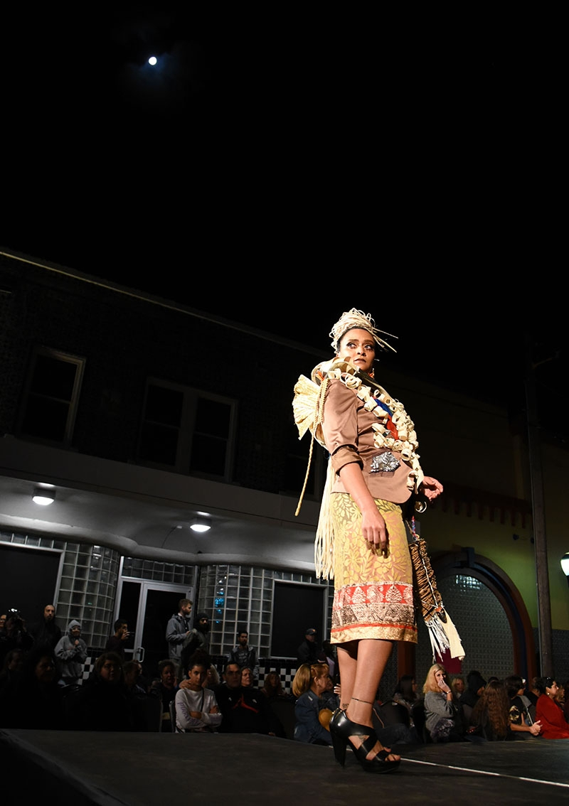 A model turns on the runway during Runway En La Calle at the 10th annual Una Noche en La Gloria Oct. 20 on Guadalupe St. <em><b>Photo by V. Finster | Heron</b></em>