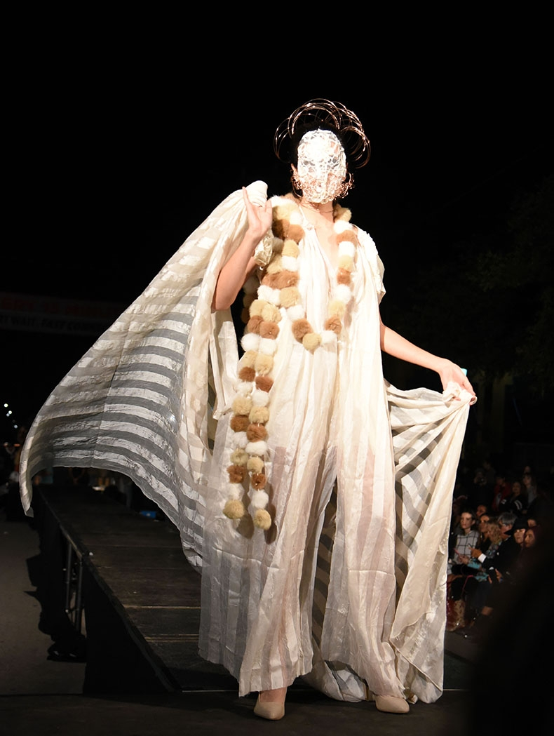 A model walks the runway during Runway En La Calle at the 10th annual Una Noche en La Gloria Oct. 20 on Guadalupe St. <em><b>Photo by V. Finster | Heron</b></em>