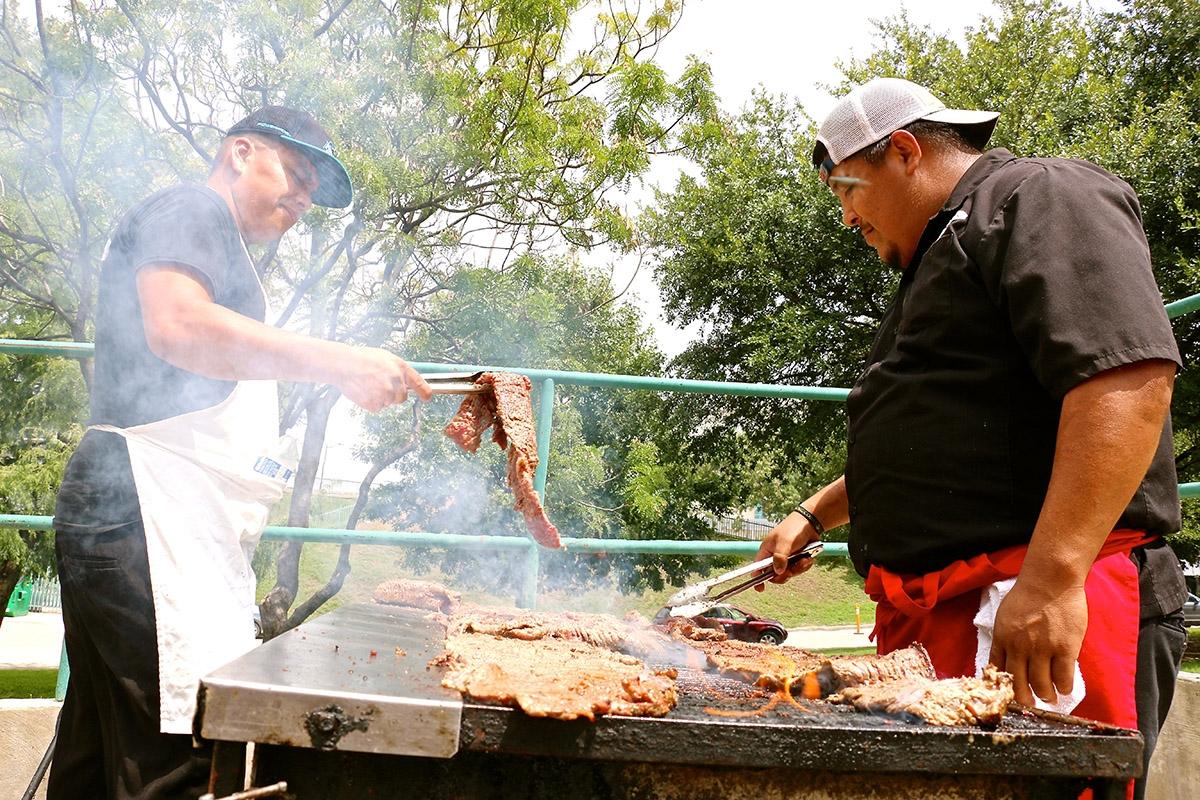 Ray  Sanchez  (left)  and  Saul  Ramirez  (right),  grill  up  meat  at  the  UTSA  vs.  Baylor  tailgate  on  September  8,  2018. <em><b>Yvonne Zamora | Heron contributor</b></em>