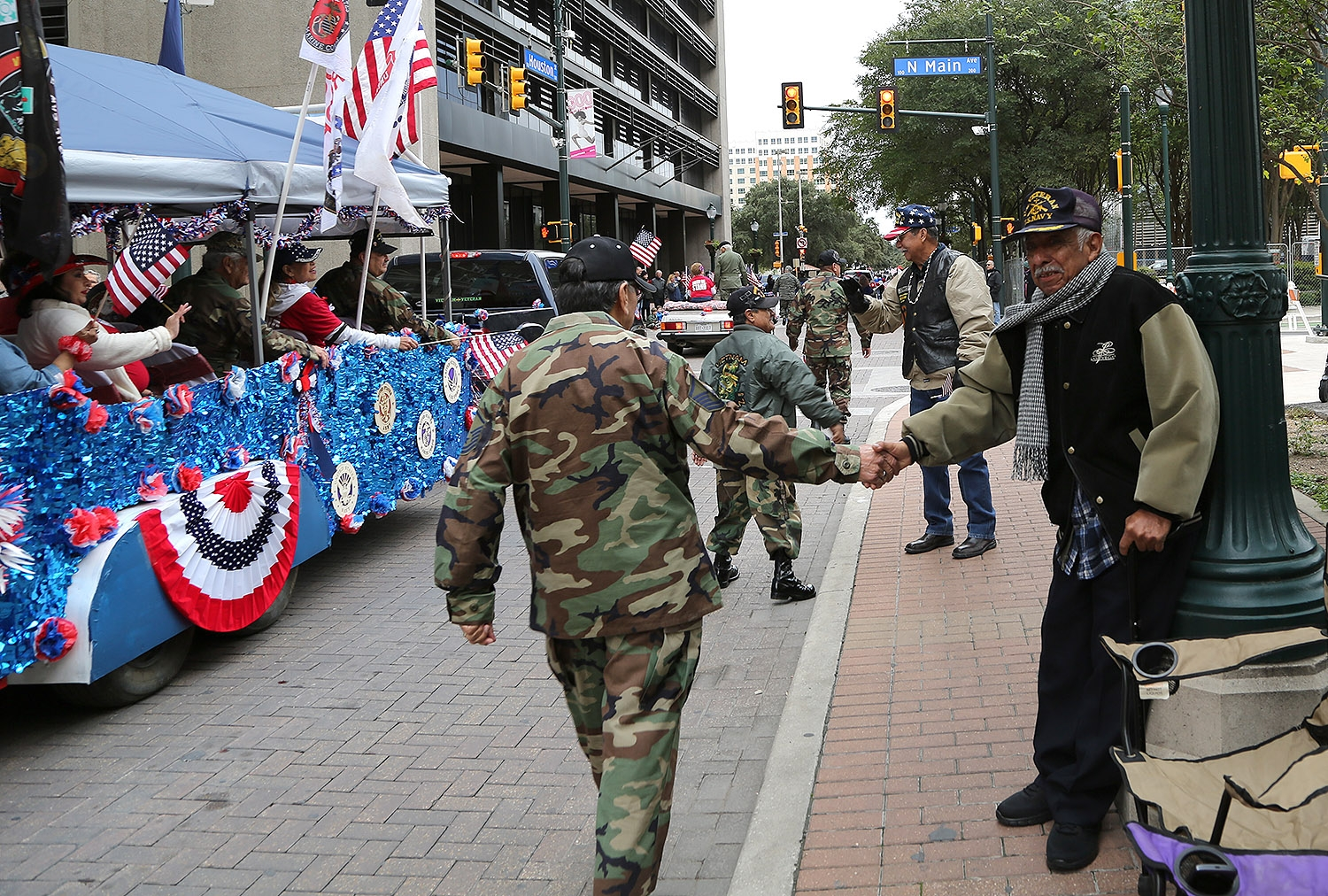 Luis Riojas, 77, A Navy veteran who served on the USS Constellation aircraft carrier in 1961-1963, greets participants of the Veterans Day Parade. <em><b>Photo by Ben Olivo | Heron</b></em>