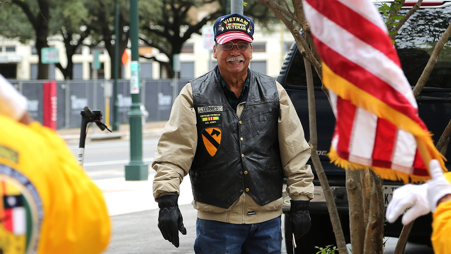 Jesse Torres, 75, greets participants of the annual Veterans Day Parade Saturday on Houston Street. Torres served in the Vietnam War in 1966-1967 with the U.S. Army's 1st Cavalry Division. <em><b>Photo by Ben Olivo | Heron</b></em>