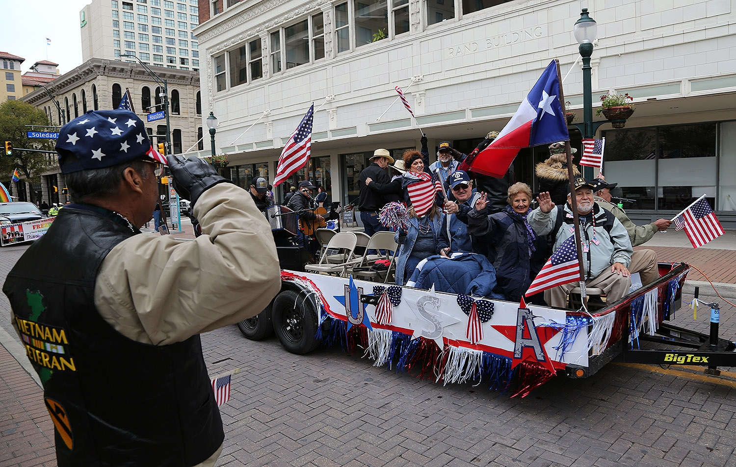 Jesse Torres, 75, salutes participants of the annual Veterans Day Parade Saturday on Houston Street. <em><b>Photo by Ben Olivo | Heron</b></em>