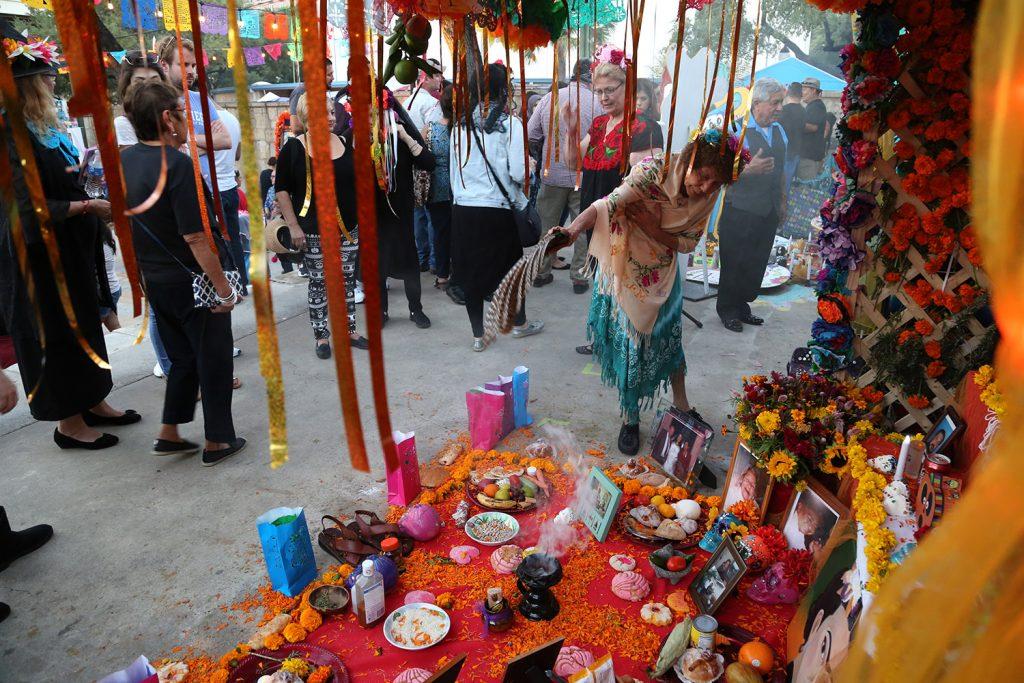 Virginia Velez fans burning incense at one of the altars at the Dia de los Muertos festival on Saturday. <em><b>Photo by Ben Olivo | Heron</b></em>