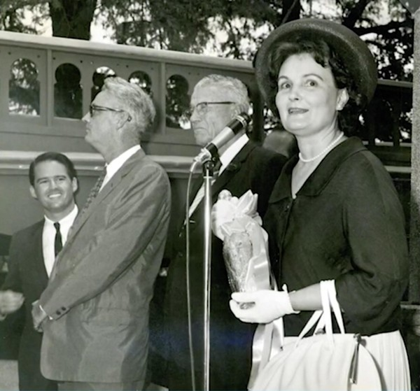 Mayor Lila Cockrell prepares to christen the San Antonio Museum of Art by breaking a bottle of beer against its façade.