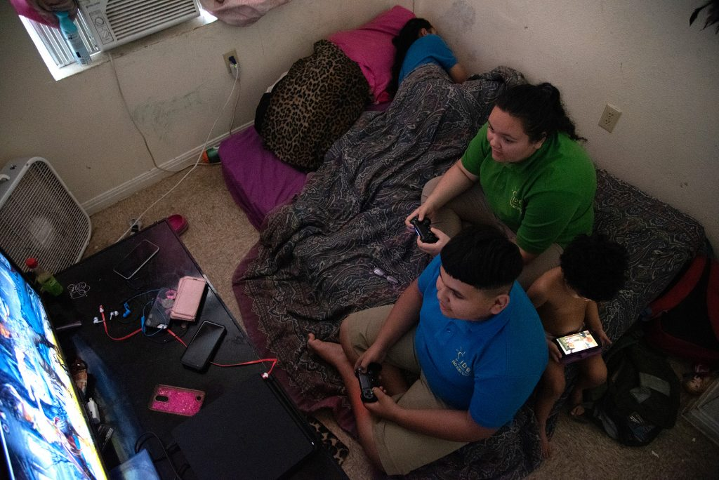 Siblings Pablo Miranda, 11, and Nadia Miranda-Colgrove, 14, play Mortal Kombat while sister Melody, 10, naps and cousin De' Andre Gant, 2, watches a movie Monday, Oct. 23 in their apartment at the Alazan-Apache Apartments.  Photo by V. Finster   Heron Contributor