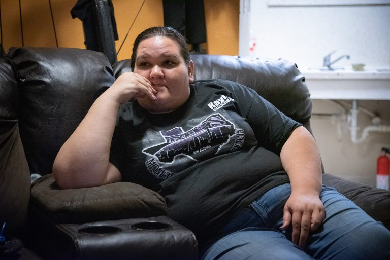 Kayla Miranda talks about her rent and fees at Alazan-Apache apartments Monday, Oct. 21 in her living room. Photo by V. Finster | Heron Contributor
