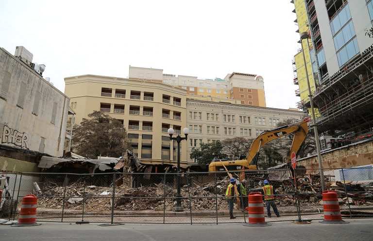 Crews demolish three buildings on the 100 block of East Commerce Street for the construction of the 17-story Floodgate luxury apartment tower. Photo by Ben Olivo   Heron