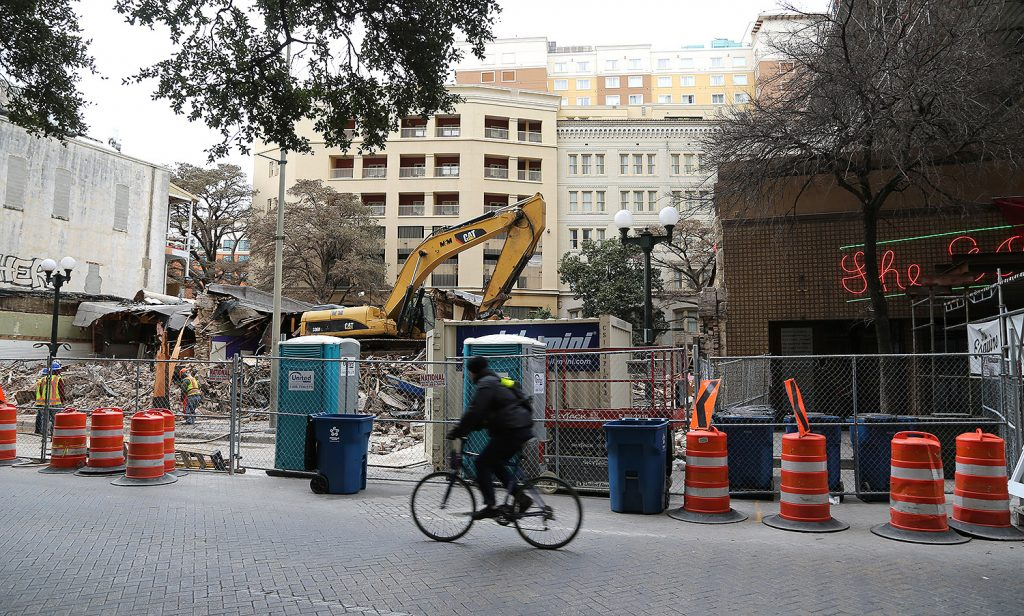 Crews demolish three buildings on the 100 block of East Commerce Street for the construction of the 17-story Floodgate luxury apartment tower. Photo by Ben Olivo | Heron