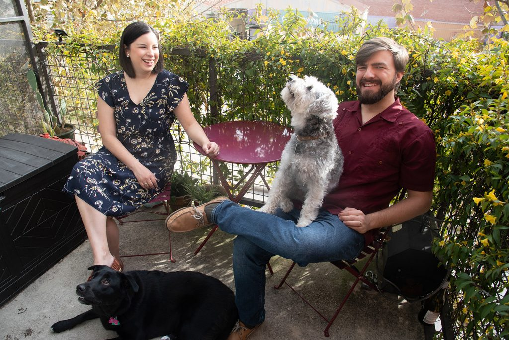 From left: Stacy Cantu-Pawlik and Joey Pawlik and pose for a photo with their dogs Stella and Otto Feb. 2 on the balcony of their residence at Broadway Lofts. Photo by V. Finster | Heron Contributor