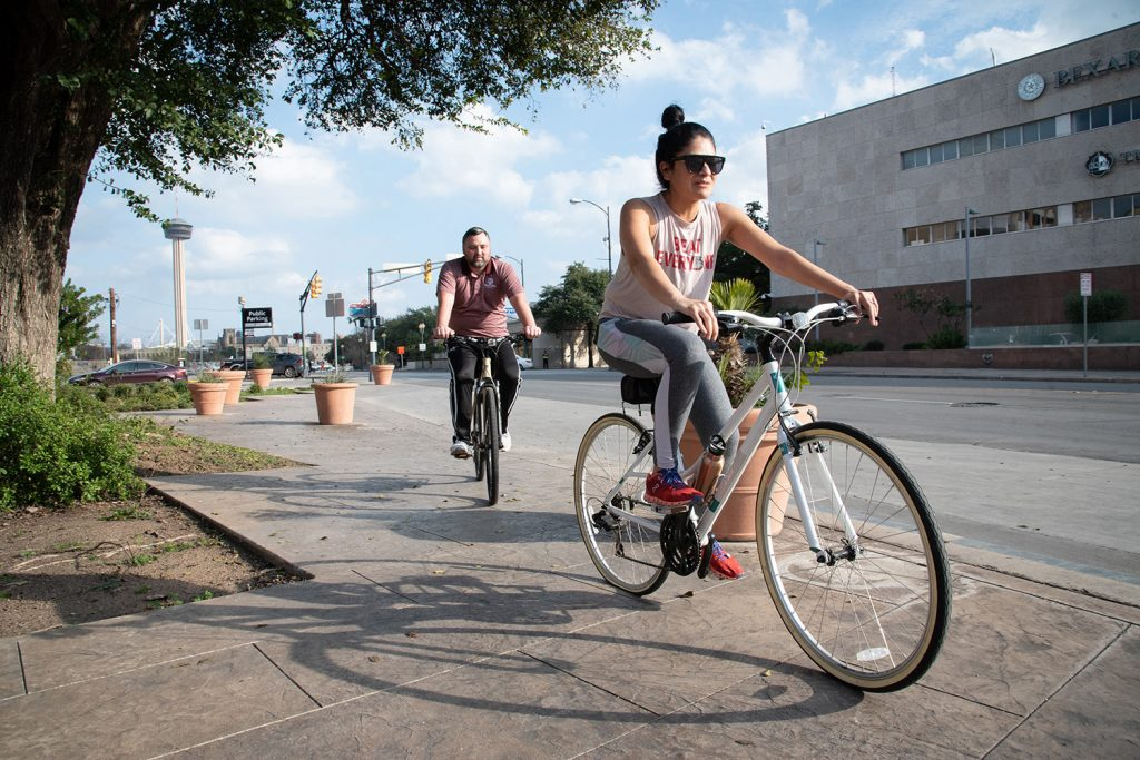 From left: Chad Miller and Mariela Delgado-Miller ride their bikes Feb. 17 at the corner on E Nueva St. Photo by V. Finster | Heron Contributor
