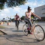 From left: Chad Miller and Mariela Delgado-Miller ride their bikes Feb. 17 at the corner on E Nueva St. Photo by V. Finster   Heron Contributor