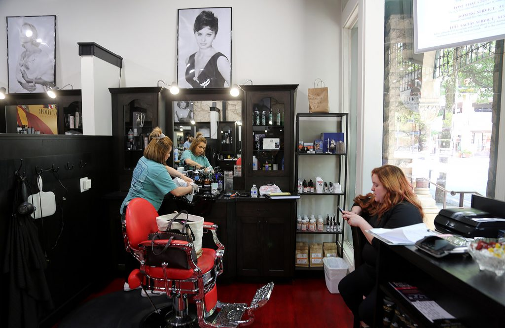 Priscilla Camareno and Christian Coronado wait for customers inside Matador Men's Grooming on Commerce Street on Tuesday, March 24, 2020, the day before they were to shut down amid coronavirus concerns. Photo by Ben Olivo | Heron