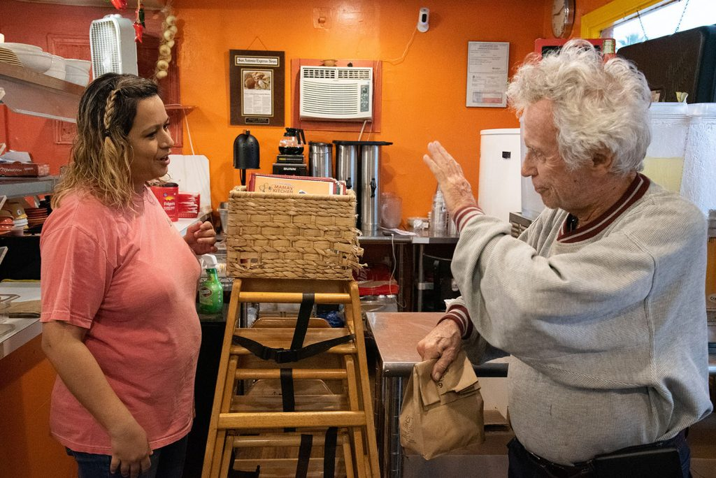 Customer Tom Keene, 85, waves to part-owner Rocio Valdez , after paying for his order inside Mama's Kitchen March 26 at 504 W. Hildebrand Ave. Photo by V. Finster | Heron Contributor