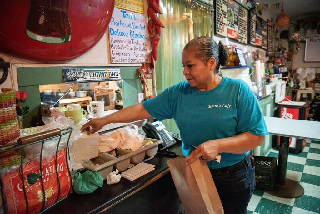 Owner Maria Beza, 59, packs an order at Maria's Cafe, March 26, at 1105 Nogalitos. Photo by V. Finster | Heron Contributor