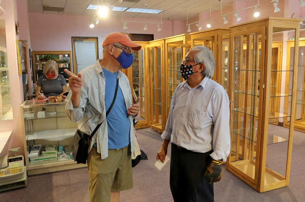 Francisco J. Mar, owner of Mar Silvery Jewelry (right), talks with Phillip Schrank, owner of Gallery Vetro, on Sunday morning.