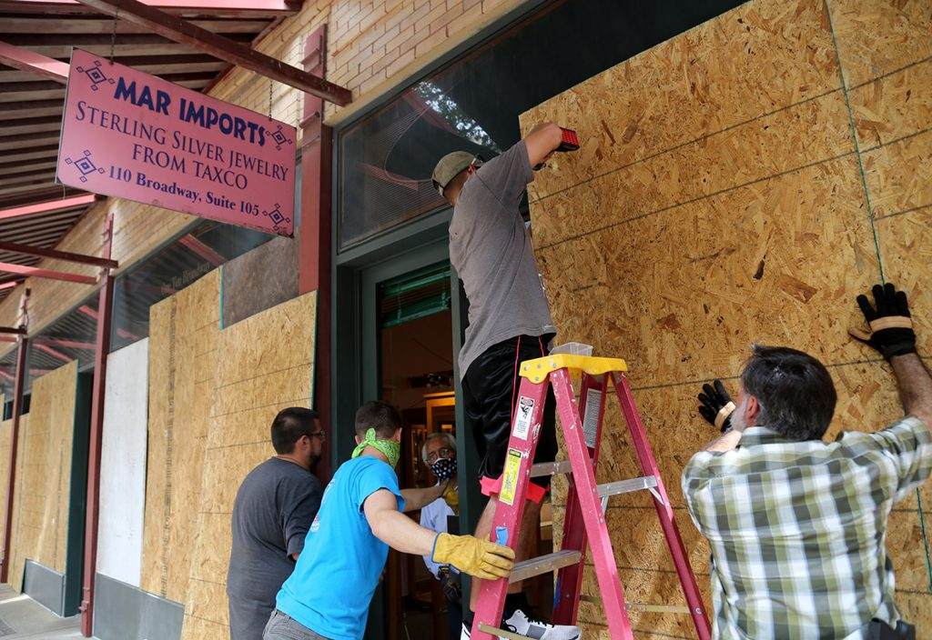Workers put plywood on Mar Silvery Jewelry on East Houston Street early Sunday morning.