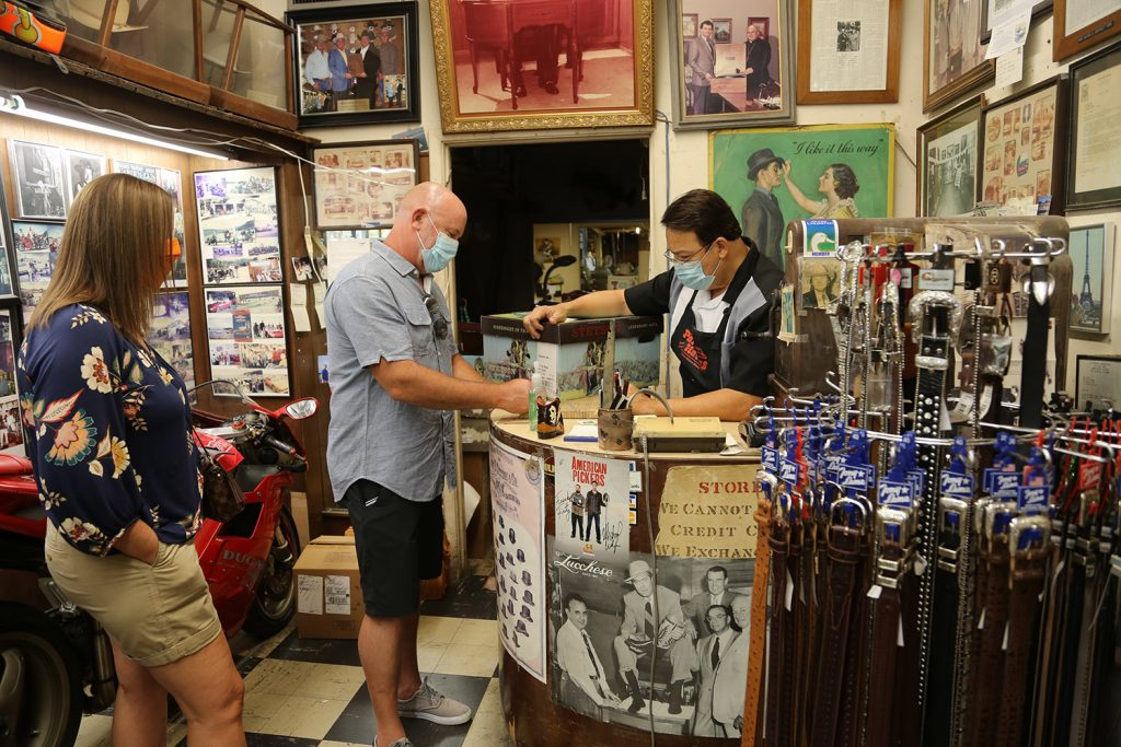 Cory and Kim Jefferies of Boerne make a purchase from Abe Cortez, co-owner of Paris Hatters, 119 Broadway, on Saturday, June 6, 2020.