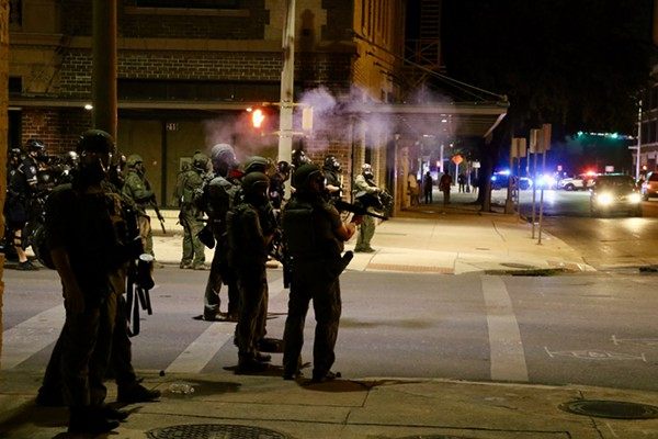 Police in riot gear stand near Alamo Plaza on Saturday night.