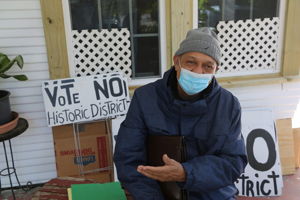 Rudolfo Ortiz sits on the porch of the home he rents on Saunders Avenue. Ortiz has spearheaded the campaign against a historic district on the near West Side.