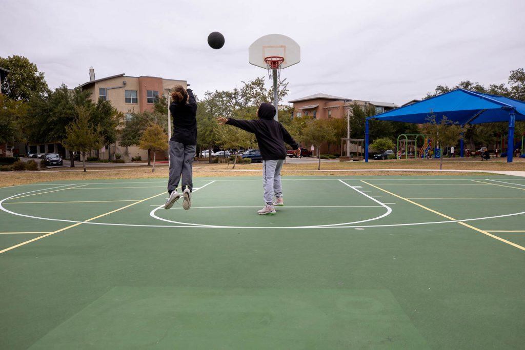 Kids play basketball at the Labor Street Park in October 2020.