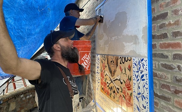 Matt Simpson spreads thin-set onto the wall of Velvet Taco while Mig Kokinda figures out which hand-stenciled tiles go on next.