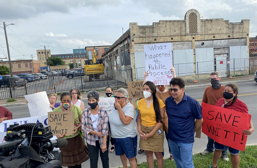 A group of historic preservationists gather to protest the potential demolition of the Whitt building in west downtown on the evening of May 28, 2021.